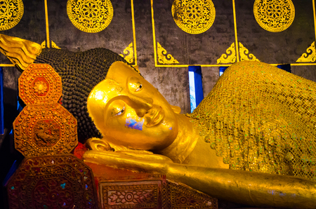 Gold yellow statue of sleeping Buddha in a sacred temple complex in East Asia Stock Photo