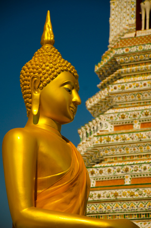 Yellow gold sitting Buddha meditating in the old ancient temple in South East Asia Stock Photo
