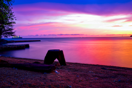 Gorgeous romantic purple orange sunset on a beach harbor in Indian Pacific sea ocean for family school children and couple honeymoon vacation