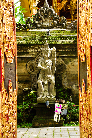 Ancient stone sculpture statue of scary beast monster with weapon guarding a sacred royal family temple entrance door