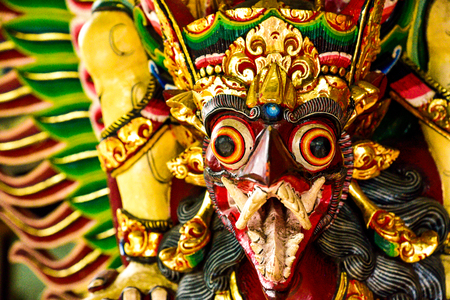 Sculptured wooden art depicting monster giant bird guarding a sacred temple in Bali Indonesia