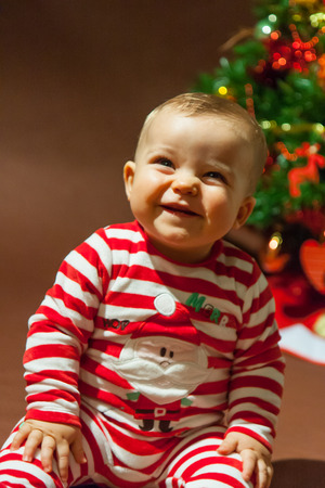 child sitting in front of Christmas tree with red and white pajamas photo