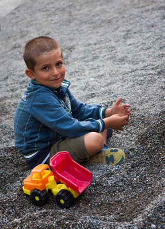 child sitting in the gravel with toy truck photo