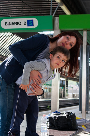 Mom and son embraced waiting for the train photo