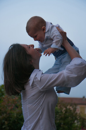 Mom and son embraced into the sky at sunset photo