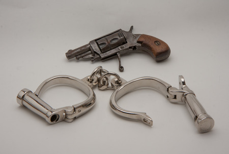 old handcuffs with locking screw English style and revolver derringer photo