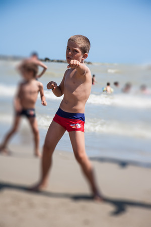 dance time: little boy dance on beach at the day time