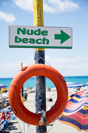 nue plage: plage de nudistes, signe indicateur sur poteau en bois avec bou�e de sauvetage d'orange