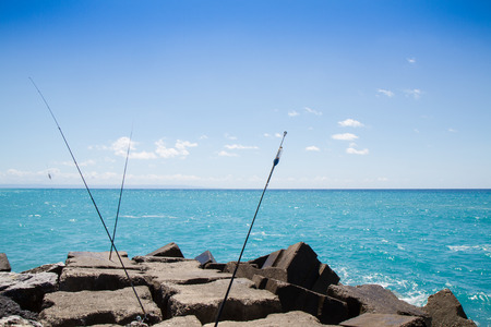 breakwaters: landscape with breakwaters, sea and blue sky and fishing rods