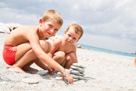 brothers playing: dos hermanos peque�os que juegan en la playa Foto de archivo