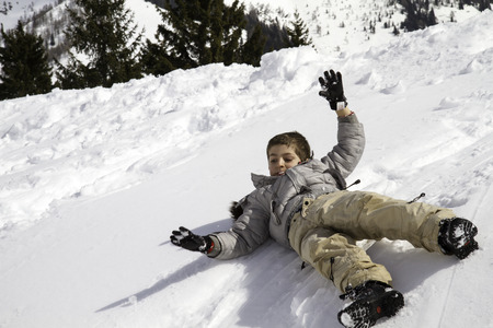 hi hat: child on snow hill that rolls, blue sky Stock Photo