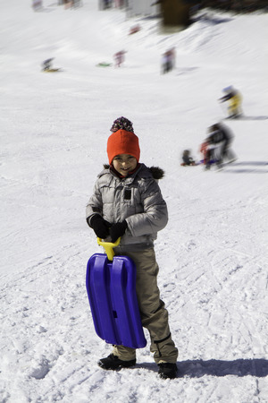 pom poms: child in the snow with blue toboggan and hat with pom poms
