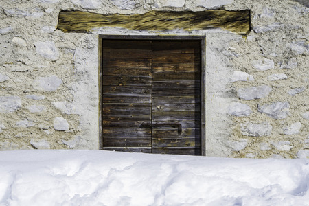 retreat: close up of a wooden door of a mountain retreat with snow Stock Photo