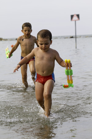 watergun: Happy childs play into sea with watergun, vacation in Italy Cesenatico