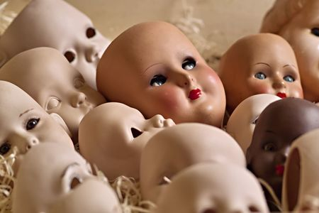 Doll heads of porcelain in a box with wood-wool