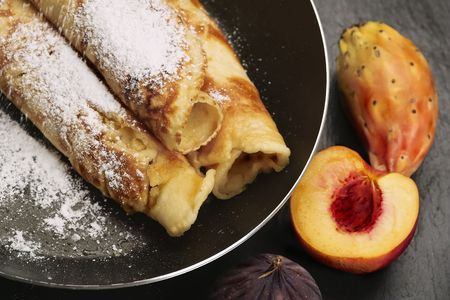 Pancakes in a frying pan with fruit and powdered sugar Stock Photo