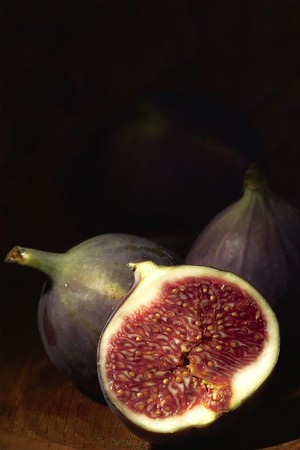 fig: fresh halved fig on dark background composition Stock Photo
