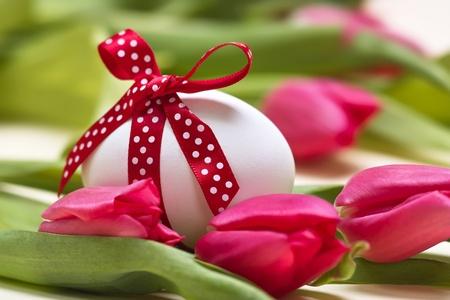 Huevo de Pascua con manchado con lazo rojo antes de tulipanes