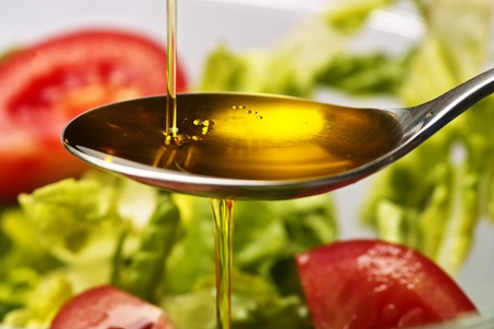 Olive oil flows into a spoon Stock Photo