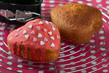 Small cake with icing and hearts decorates on a baking rust
