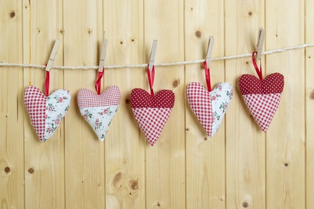 Five colored cotton hearts hang on a cord before a  wooden wall  The hearts are fastened with clothespins
