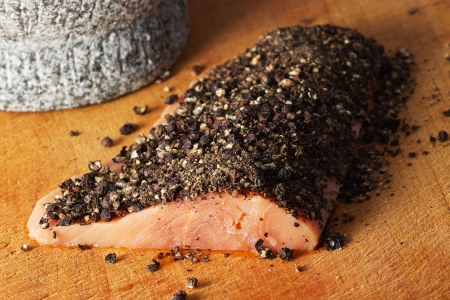 On a culinary board there lies a salmon fillet with a pepper crust  In the left background there is a culinary mortar  Stock Photo