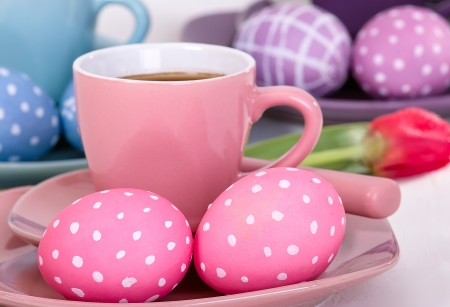 In the foreground a cup of coffee with two Easter eggs  In the background other eggs and a recumbent tulip