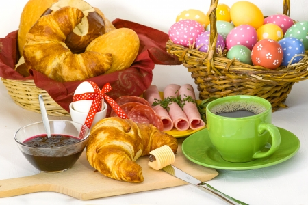 Colored Easter breakfast with Easter eggs, coffee, croissant, ham and jam Stock Photo