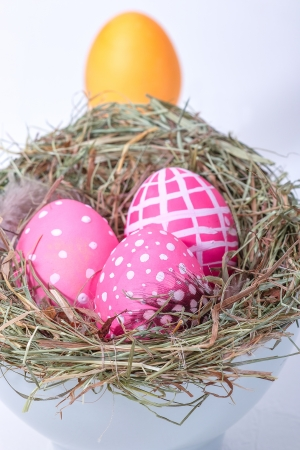 Three Easter eggs in a nest  In the background other eggs on white