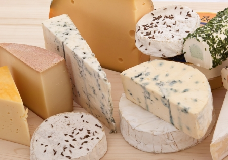 Many cheese kinds on a wooden plate