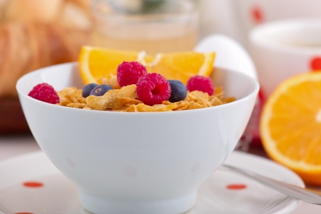 A plate with cornflakes and fresh raspberries and bilberries on a breakfast table