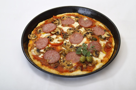 Freshly baked pizza in a pizza shape, topped with tomato, cheese, salami, olive, mushroom, onion, garnished with two olives and a bunch Rosemary and Marjoram  Isolated on a white