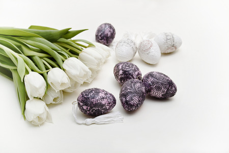 A bouquet of white tulips next to the decorated Easter eggs on a light background is. The image was photographed in the landscape format.  Stock Photo