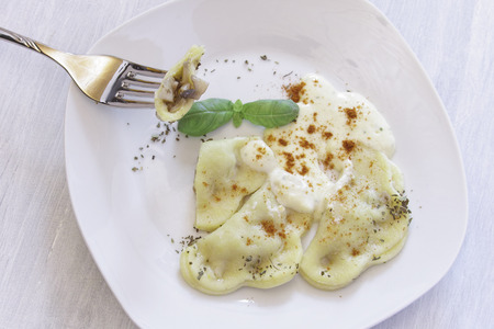 Homemade Ravioli with cheese and cream sauce on a white plate. At the right edge of the dish knife and fork are stored. photo