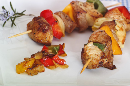 Shish kebab on a white plate with peppers, onions and spices