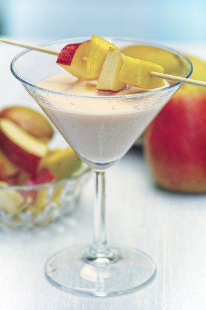 A glass of mango PEAR shake. Diagonally above the glass there are several pieces of fruit, which are skewered on a stick.
