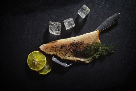 fish type: On a black background, a Trout Fillet with dill, lemon, ice cubes is garnished. Stock Photo