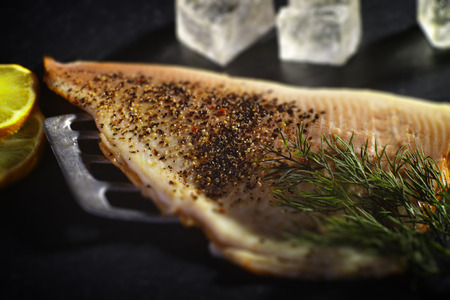 On a black background, a Trout Fillet with dill, lemon, ice cubes is garnished. Stock Photo