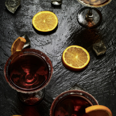 Red cocktail with orange slices on a wet, black stone