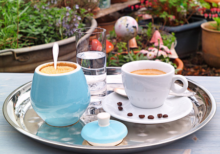 Cup of Coffee on a silver plate and a  glass of water and a sugar bowl