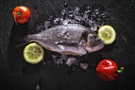 Dorade with lemon and tomato on black slate