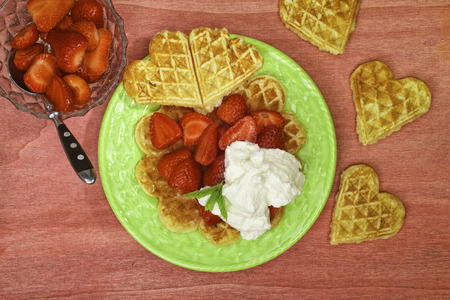 waffles with strawberries and cream on a green plate photographed in Top view
