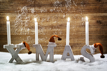 Four burning candles on the letter XMAS