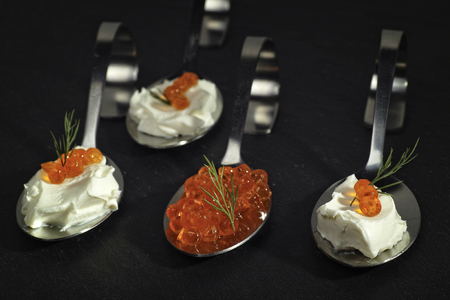 Red caviar on two bent spoons