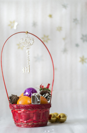 christmas ornamentation: Red wicker basket with gifts and tangerines
