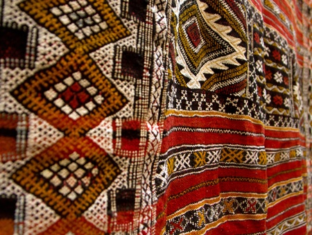 Red carpets stacked in a traditional store. On carpet is  typical pattern from Africa area. photo