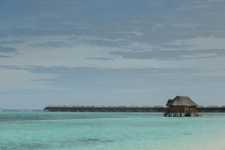 Turqoise indian sea with water villas and whole resorts located on  Picture taken with very low horizontal line