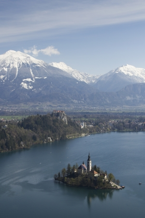 Picture of church located at Bled in Slovenia. Picture in verticla position with a lot of snow in mountains photo