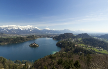 Picture of  Bled Lake and church taken from air view. On picture is whole lake and forrest around lake with a lot of empty space on top of picture photo