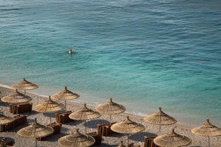 Crystal clear sea of Albania, with  wodden umbrellas and undefined swimmer